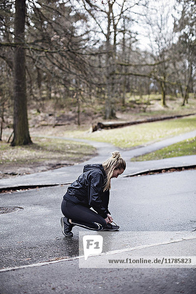 Durchgehende Seitenansicht der Sportlerin beim Schnürsenkelbinden auf der Straße im Wald