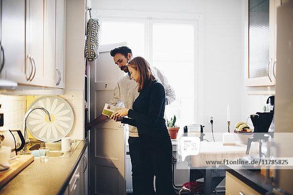Frau zeigt dem Mann in der Küche zu Hause Lebensmittelverpackung
