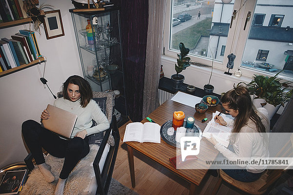 High angle view of young female students studying in college dorm room