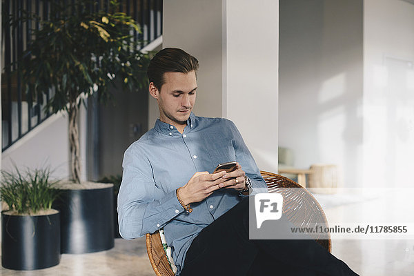 Businessman using smart phone while sitting on chair in office