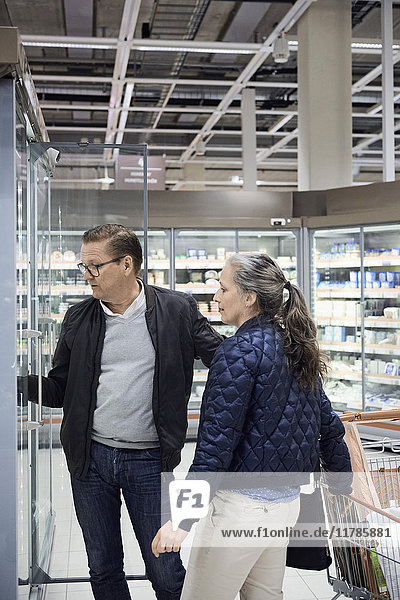 Ein reifes Paar steht neben dem Einkaufswagen im Supermarkt.