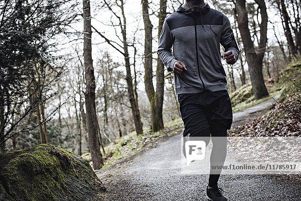 Niedriger Abschnitt des männlichen Athleten  der auf einer schmalen Straße im Wald läuft.