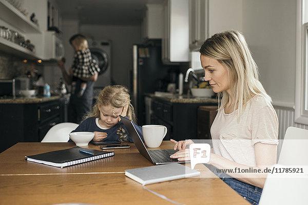 Frau  die den Laptop benutzt  während die Tochter mit der Familie im Hintergrund zu Hause frühstückt.