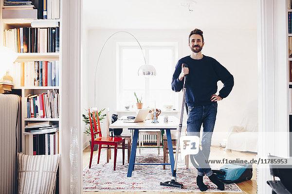 Porträt eines glücklichen Mannes mit Staubsauger im Esszimmer zu Hause