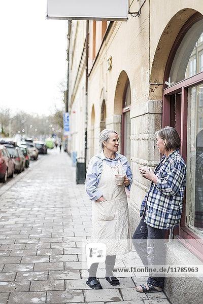 Fröhliche Kolleginnen stehen mit Kaffeetassen auf dem Fußweg beim Keramikladen in der Stadt