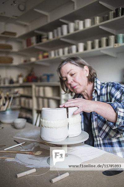 Reife Töpferin bei der Arbeit an der Vase auf dem Tisch in der Werkstatt