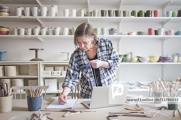Reife Töpferin schreibt auf Papier  während sie am Tisch in der Werkstatt am Laptop steht