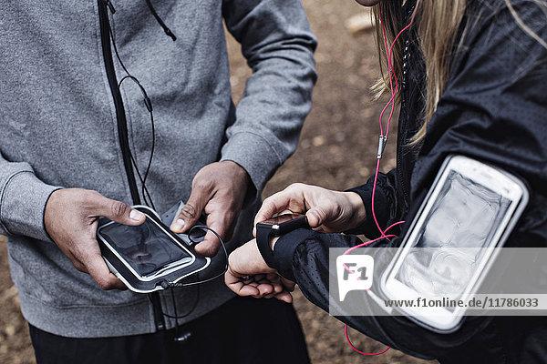 Mittelteil der Athleten mit Smart Watch und Handy im Wald