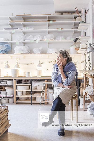 Senior Töpferin schaut weg,  während sie auf dem Hocker gegen die Regale in der Werkstatt sitzt.