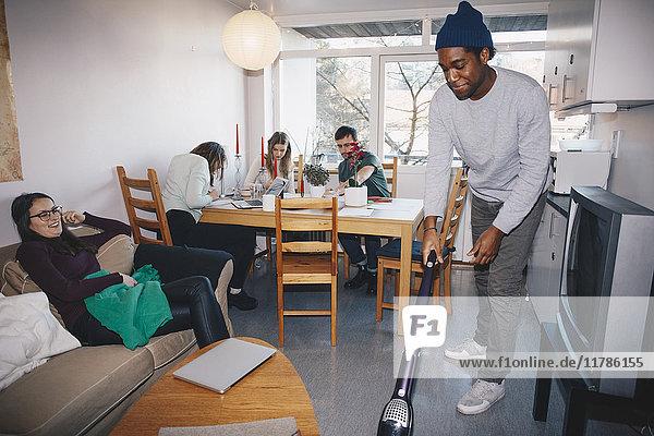 Mann putzt den Boden  während Freunde im Studentenwohnheim sitzen.