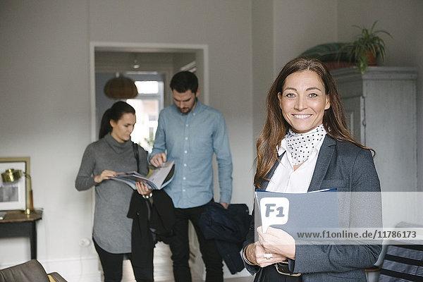 Porträt einer lächelnden reifen Immobilienmaklerin mit einem Paar  das im Hintergrund diskutiert.