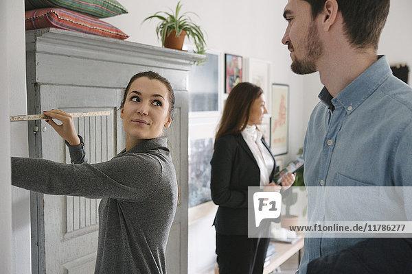 Mann betrachtet Frau mit Maßband und Maklerin im Hintergrund