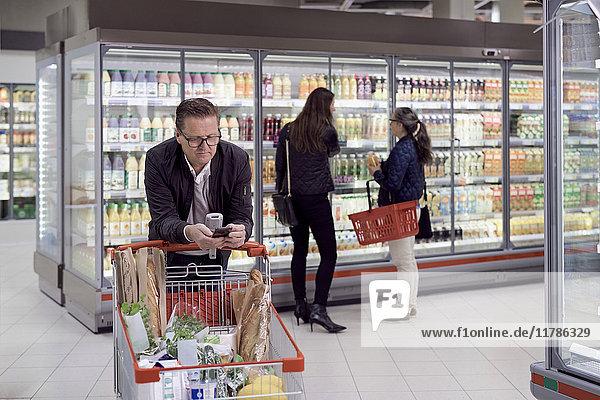 Reifer Mann  der das Handy benutzt  während er sich auf den Einkaufswagen lehnt  gegen Frauen  die Säfte im Kühlregal im Supermarkt kaufen.