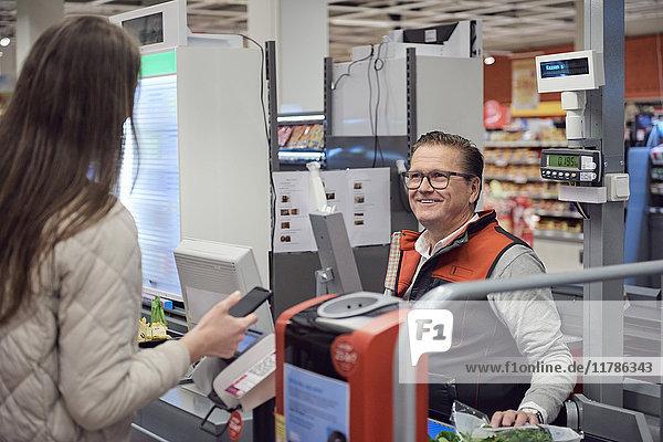 Reife Kassiererin beim Bezahlen durch kontaktloses Bezahlen im Supermarkt