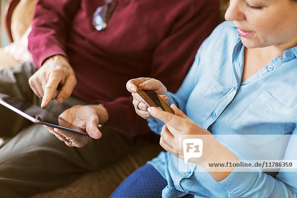 Ansicht des älteren Mannes beim Online-Shopping mit Tochter über Kreditkarte und digitales Tablett