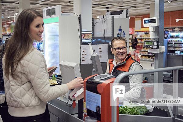 Reife Kassiererin und Frau an der Kasse beim Blick in den Supermarkt