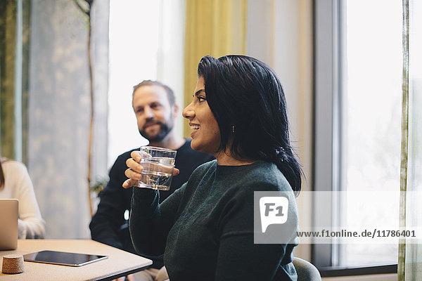 Lächelnde Geschäftsfrau hält ein Glas Wasser  während sie mit Kollegen am Konferenztisch sitzt.