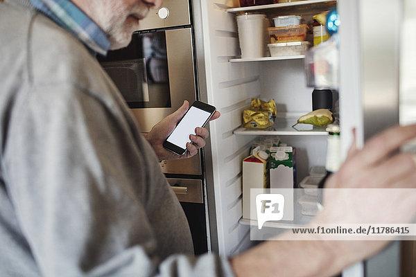 Senior Mann hält Telefon während der Suche im Kühlschrank zu Hause
