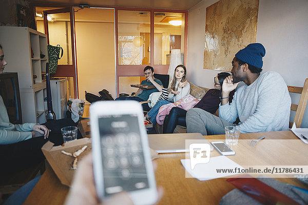 Gestutzte Hand Frau hält Handy gegen Freunde im Studentenwohnheim Zimmer