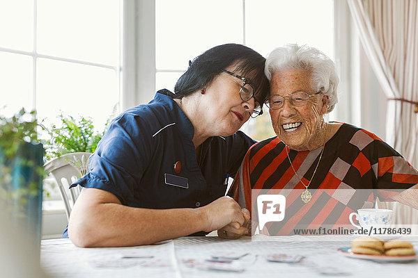 Glückliche Hausmeisterin und Seniorin am Tisch sitzend