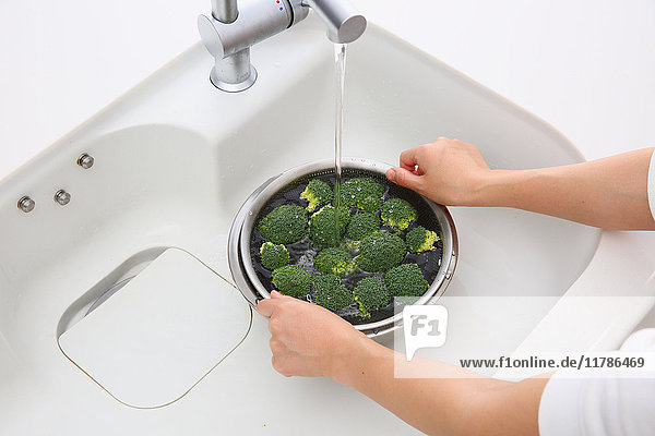 Japanese woman washing broccoli in the kitchen