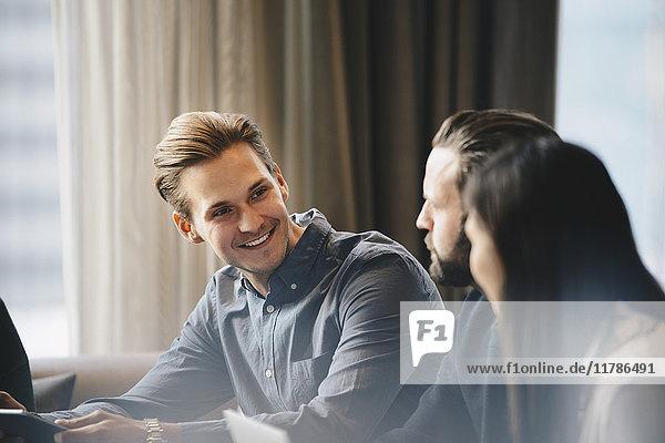 Glücklicher Geschäftsmann im Gespräch mit Kollegen im hell erleuchteten Büro