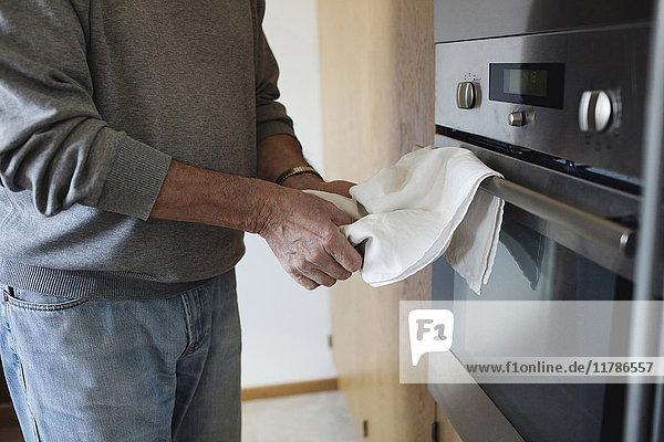 Mittelteil des Mannes  der die Hände wischt  um auf der Mikrowelle in der Küche zu trocknen.