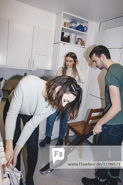 Junge Mitbewohner reinigen Küche im Studentenwohnheim