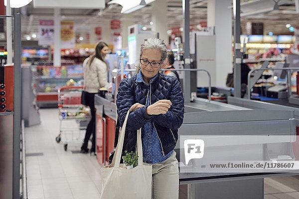 Lächelnde reife Frau mit Einkaufstasche im Supermarkt