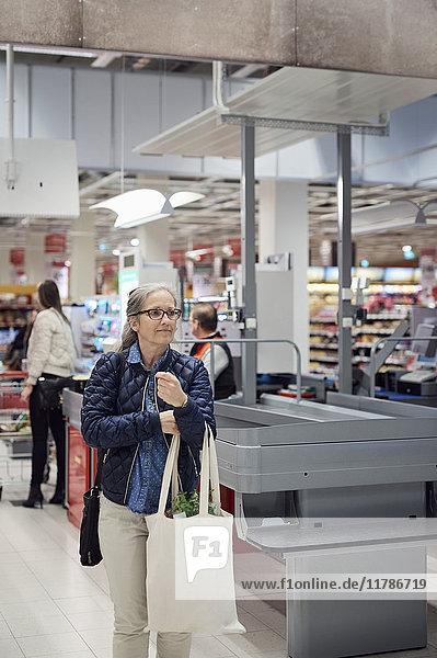 Reife Frau mit Einkaufstasche beim Gehen an der Kasse im Supermarkt