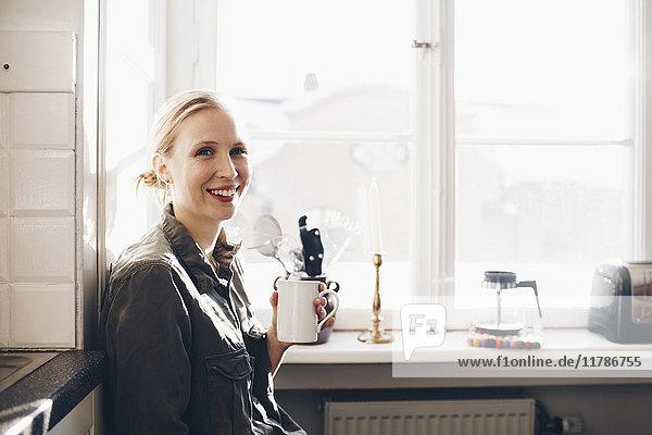Glückliche Frau mit Kaffeetasse gegen Fenster in der Küche zu Hause