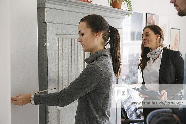 Immobilienmaklerin und Mann mit Blick auf die Frau mit Maßband zu Hause