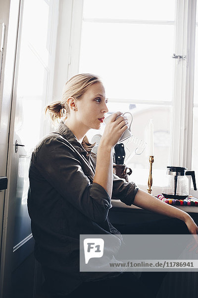 Side view of woman drinking coffee against window in kitchen at home
