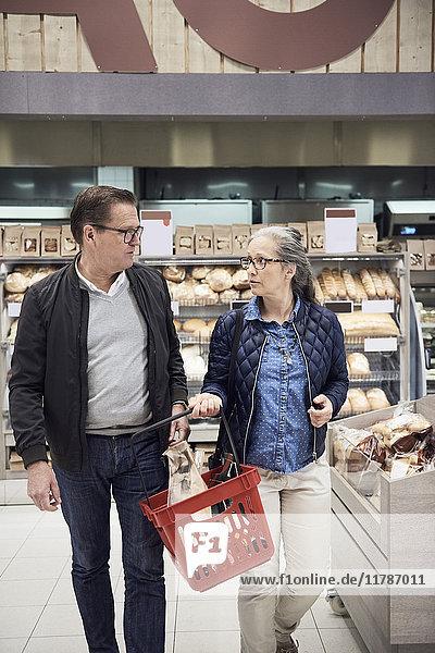 Reife Paare beim Spazierengehen mit dem Korb im Supermarkt