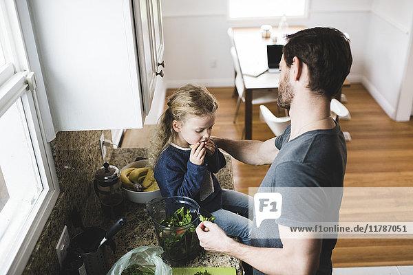 Hochwinkelansicht des Vaters beim Kochen  während die Tochter Früchte in der Küche hat.