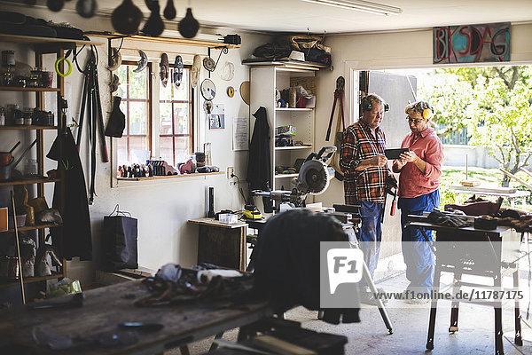 Volle Länge des Seniorenpaares mit digitalem Tablett in der Werkstatt