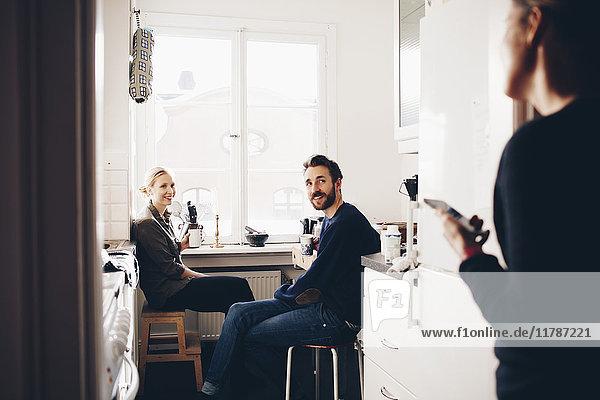 Ein glückliches Paar sitzt in der Küche und schaut eine Freundin an.