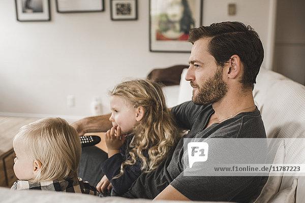 Mittlerer erwachsener Vater mit Töchtern  die zu Hause im Wohnzimmer fernsehen.