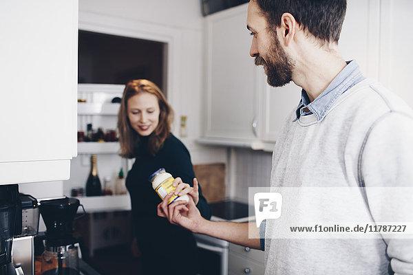 Mann gibt der Frau in der Küche zu Hause ein Glas zu essen