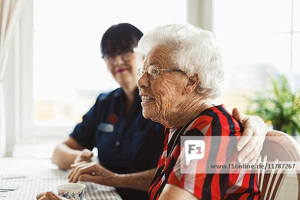 Seitenansicht der glücklichen Seniorin mit Hausmeisterin zu Hause