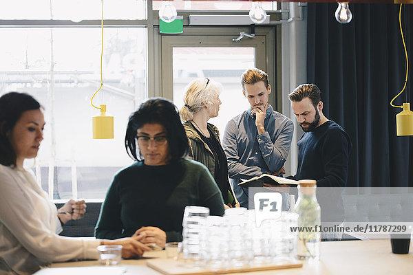 Geschäftskollegen beim Lesen im hell erleuchteten Büro