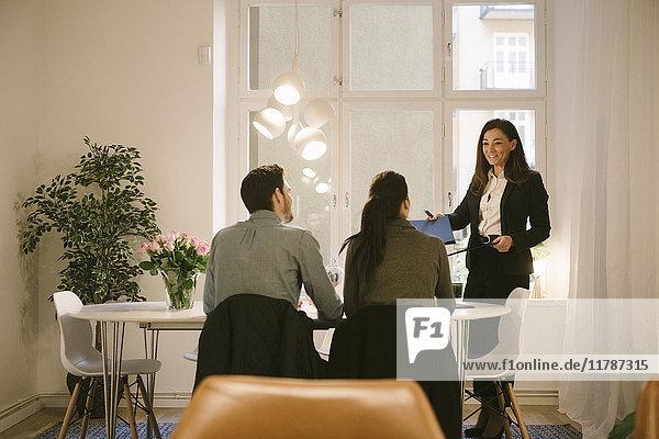 Lächelnde Maklerin und junges Paar diskutieren im Büro