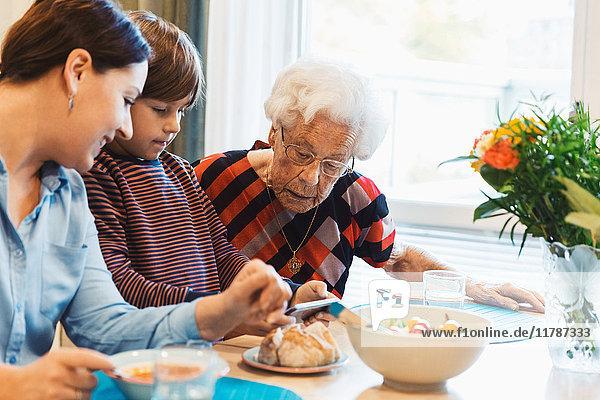 Urgroßmutter und Mutter schauen den Jungen mit dem Smartphone im Haus an.