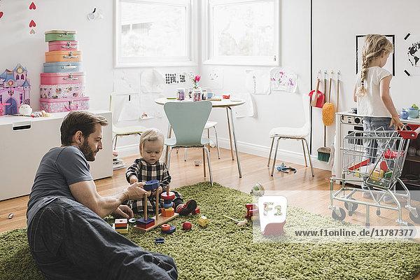 Vater und Töchter spielen mit Spielzeug im Spielzimmer zu Hause