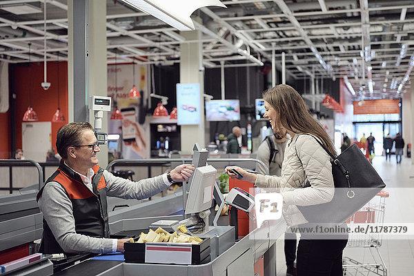 Reife Kassiererin im Gespräch mit der Frau beim Bezahlen an der Kasse im Supermarkt