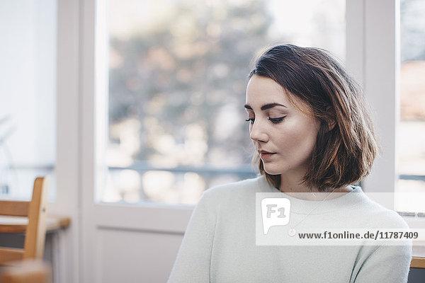 Frau sitzt am Fenster im Studentenwohnheim