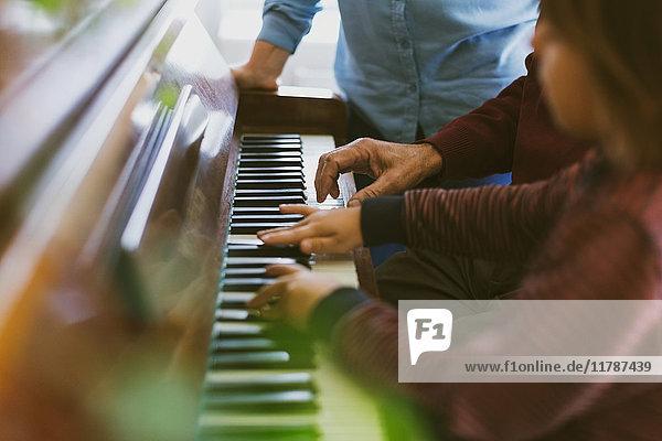 Mittelteil der Frau neben dem Jungen und Urgroßvater beim Klavierspielen