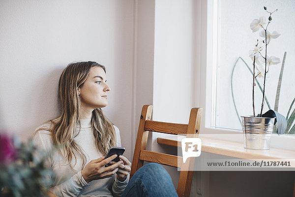 Junge Frau sitzt mit Handy auf dem Stuhl und schaut durchs Fenster in den Schlafsaal.