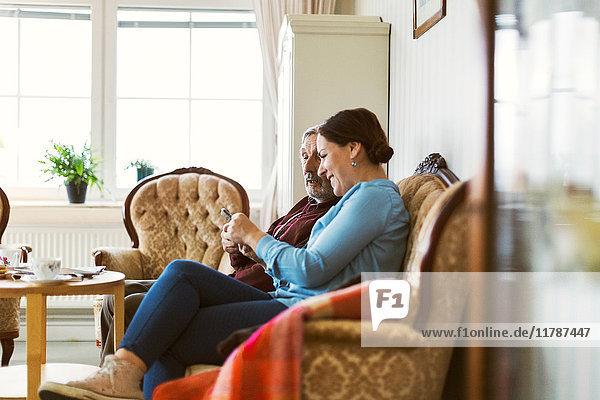 Seitenansicht eines älteren Mannes mit Smartphone und Tochter im Wohnzimmer