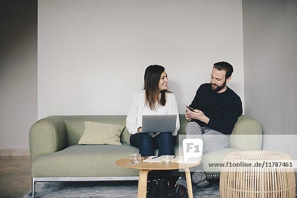 Geschäftskollegen diskutieren auf dem Sofa gegen die weiße Wand in der Bürolobby